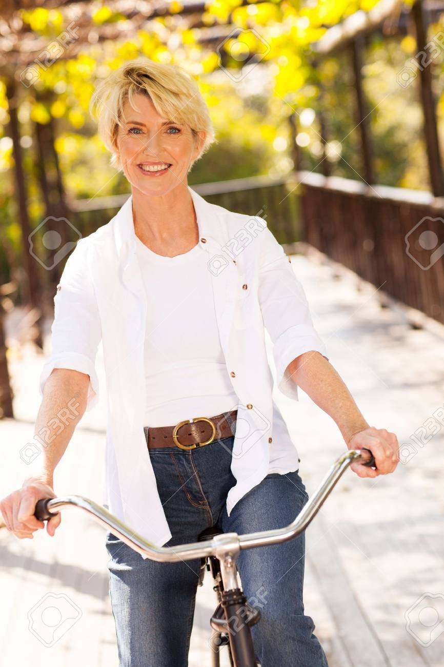 beautiful mature woman riding a bike outdoors stock photo, picture