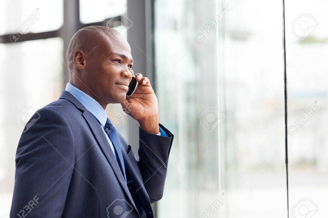 handsome african american businessman talking on mobile phone in modern office Stock Photo - 23152729