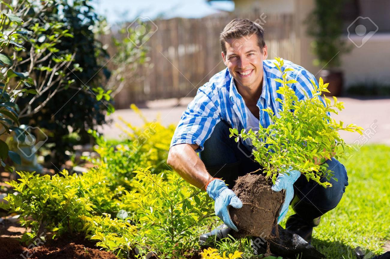gardening gloves happy young man gardening in backyard stock photo