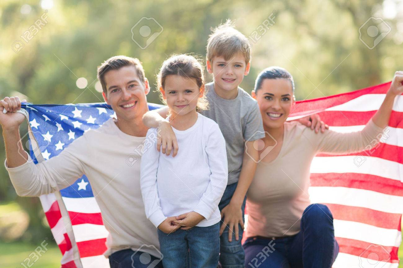 Portrait of beautiful modern american family with usa flag outdoors stock photo 28819279