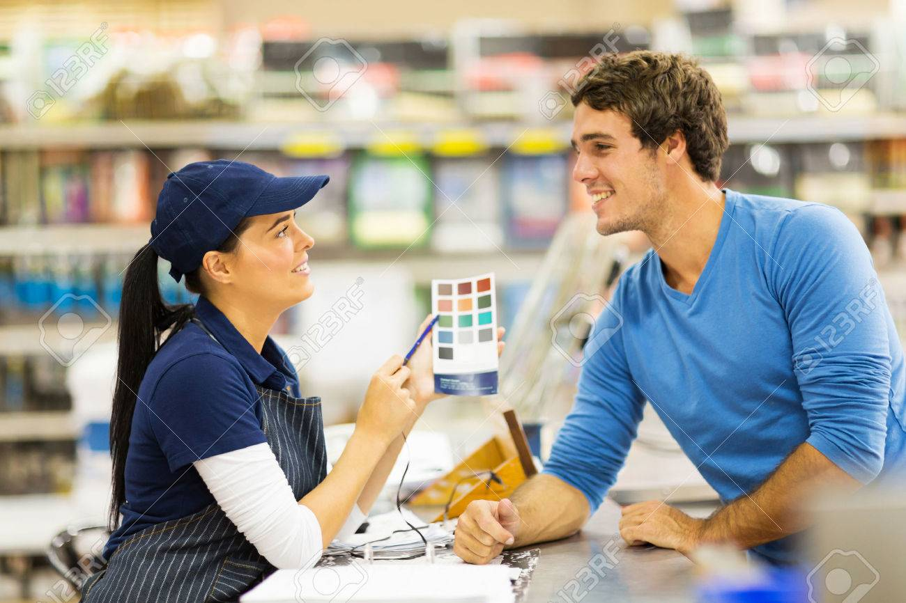 pretty paint store assistant helping customer choose paint color stock photo pretty paint store assistant helping customer choose paint color