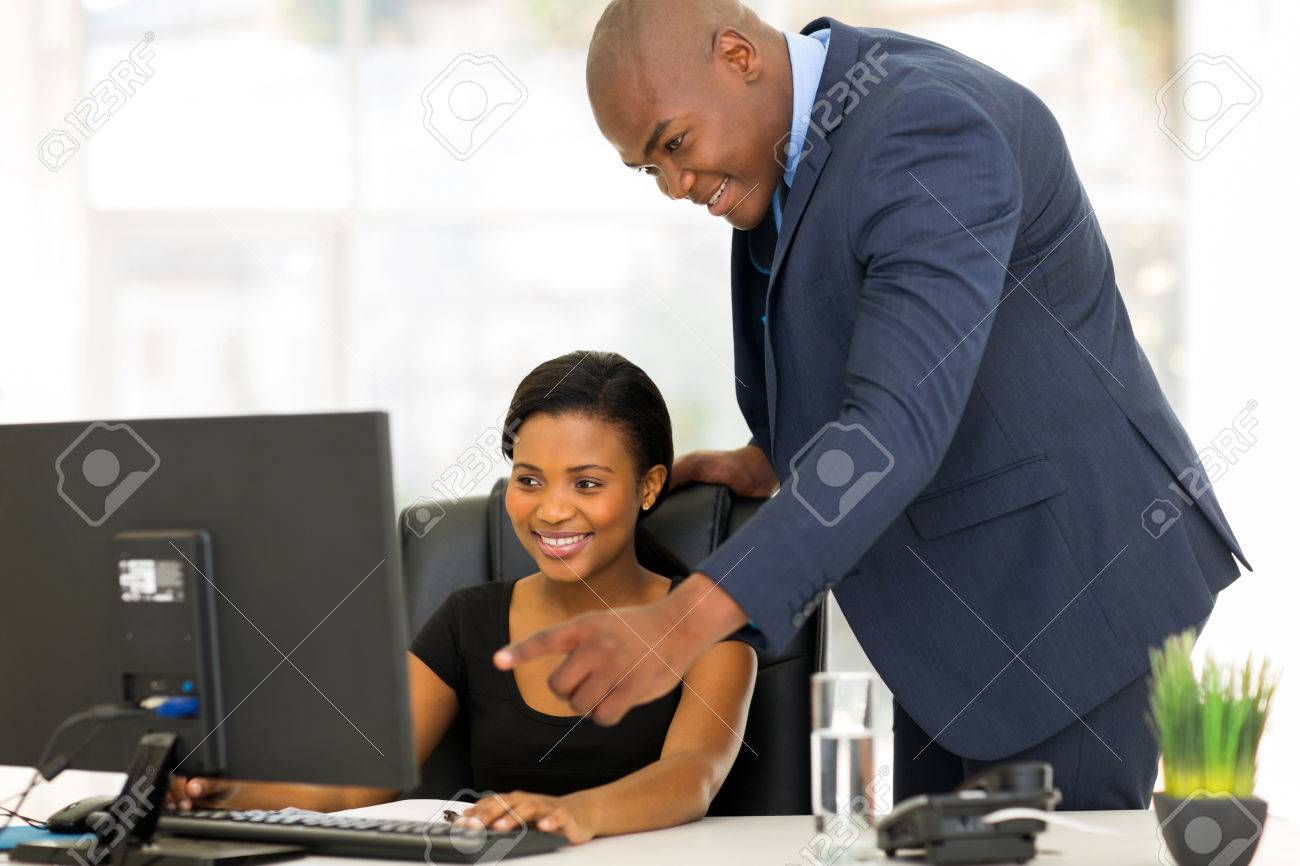 friendly african boss guiding his new employee her work stock stock photo friendly african boss guiding his new employee her work