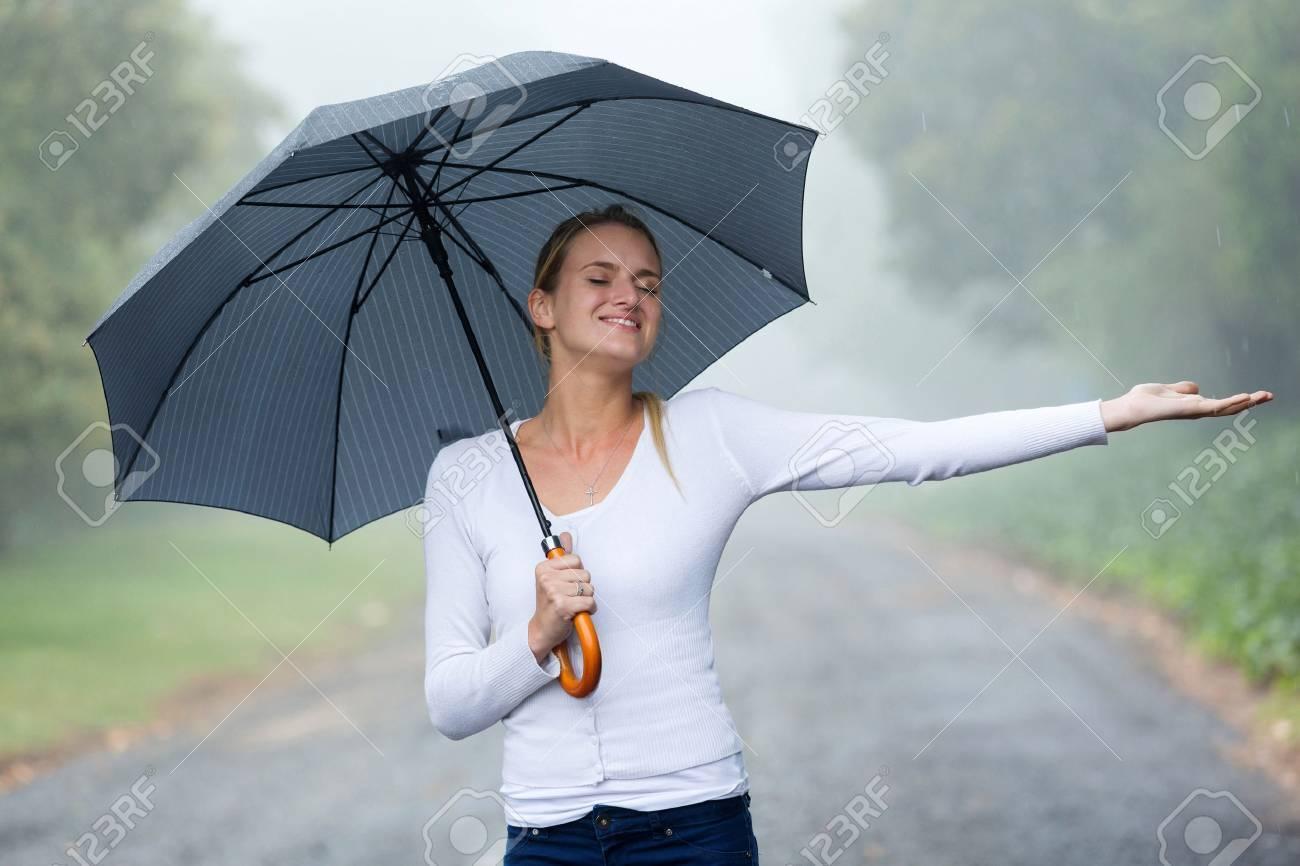 10811b17c76 attractive woman with umbrella enjoying the rain Stock Photo - 37930551