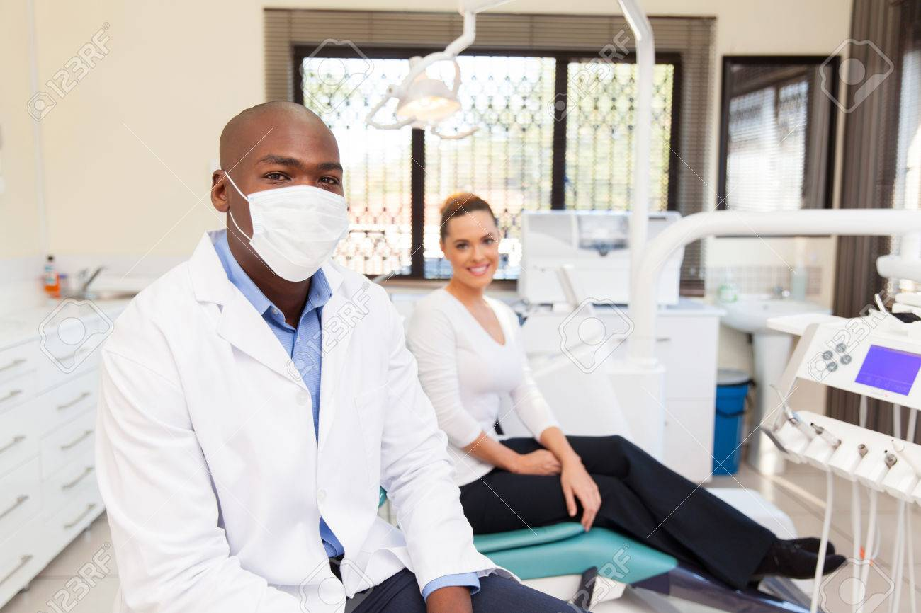 Professional African American Dentist And Patient In Office Stock Photo