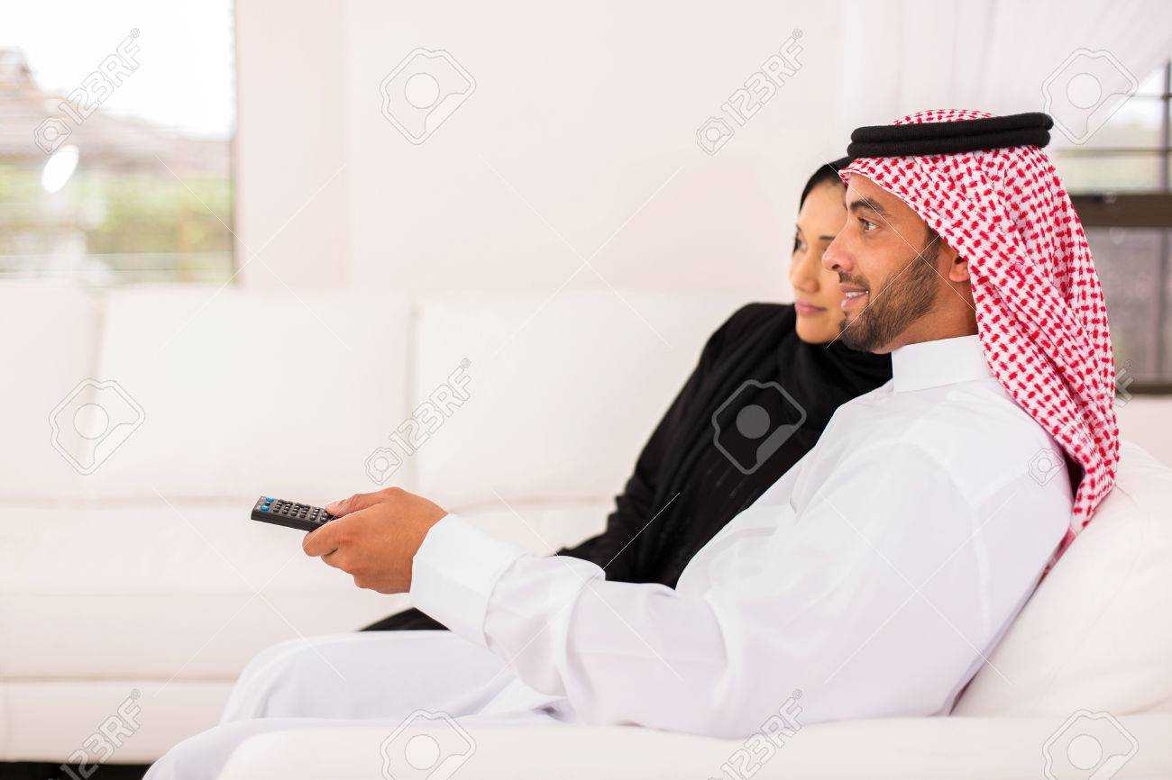 Side View Of Arabian Couple Watching Tv In The Living Room At ...