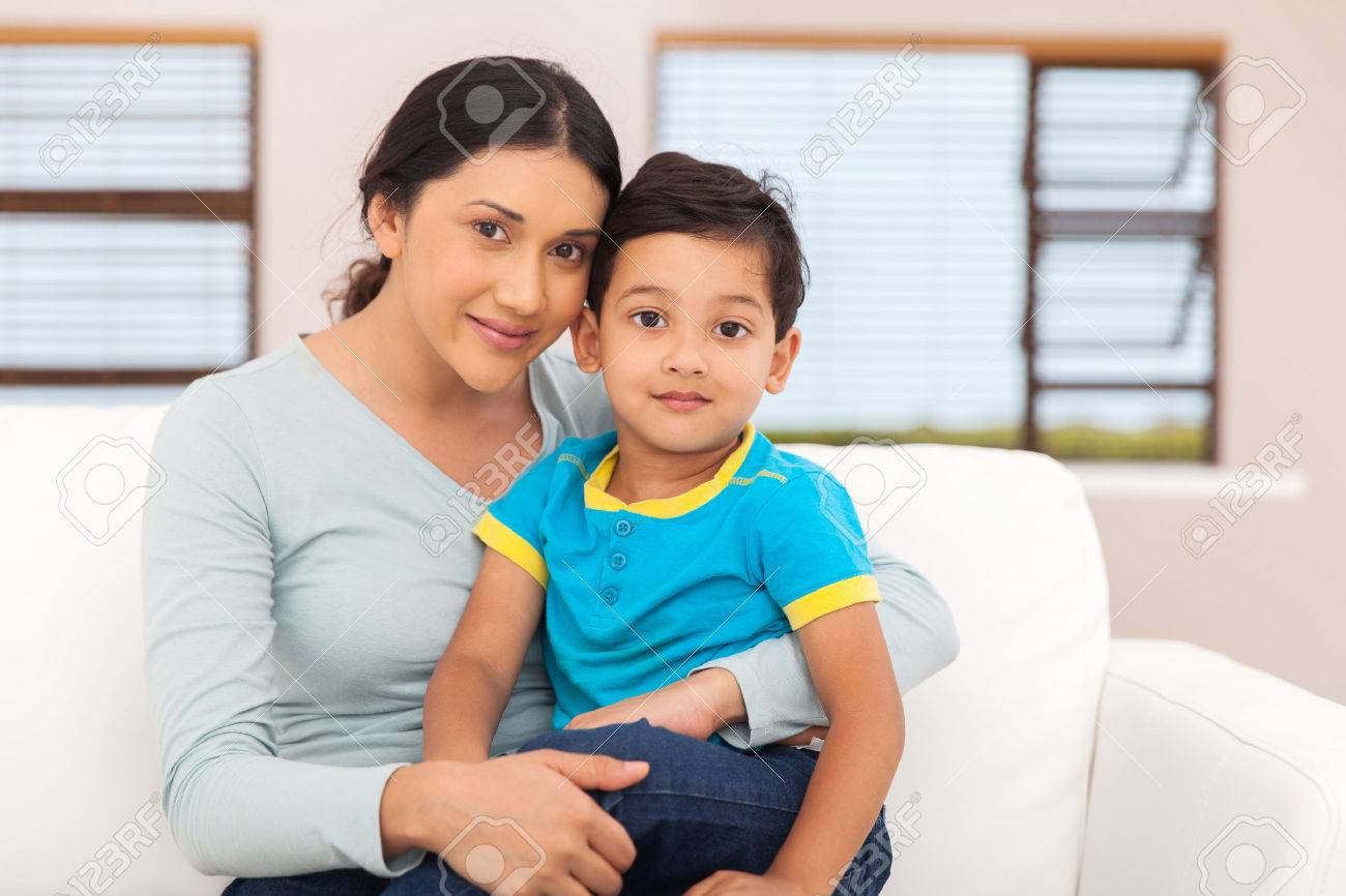 portrait of beautiful indian mother and little boy sitting at home - 49813131