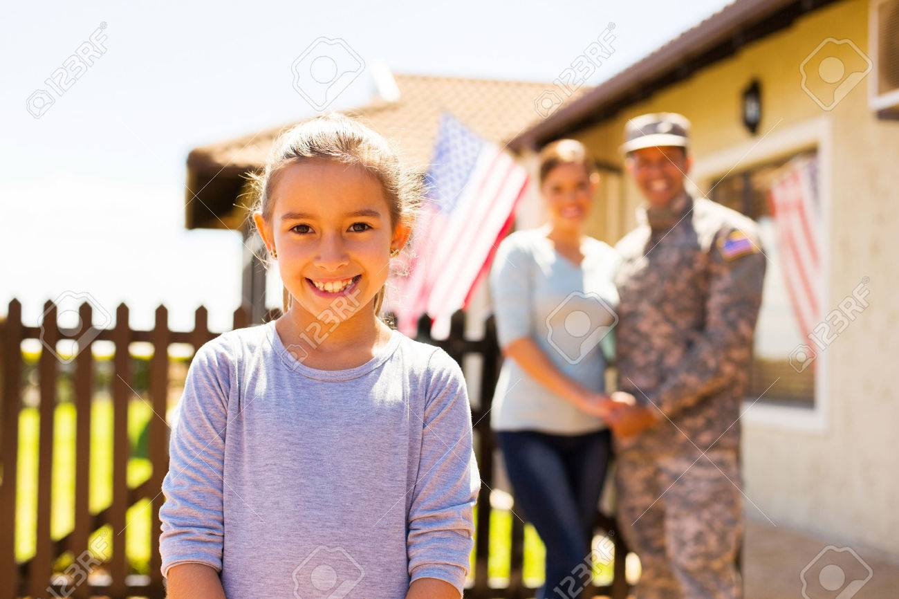 adorable little girl standing in front of parents outdoors - 50864661