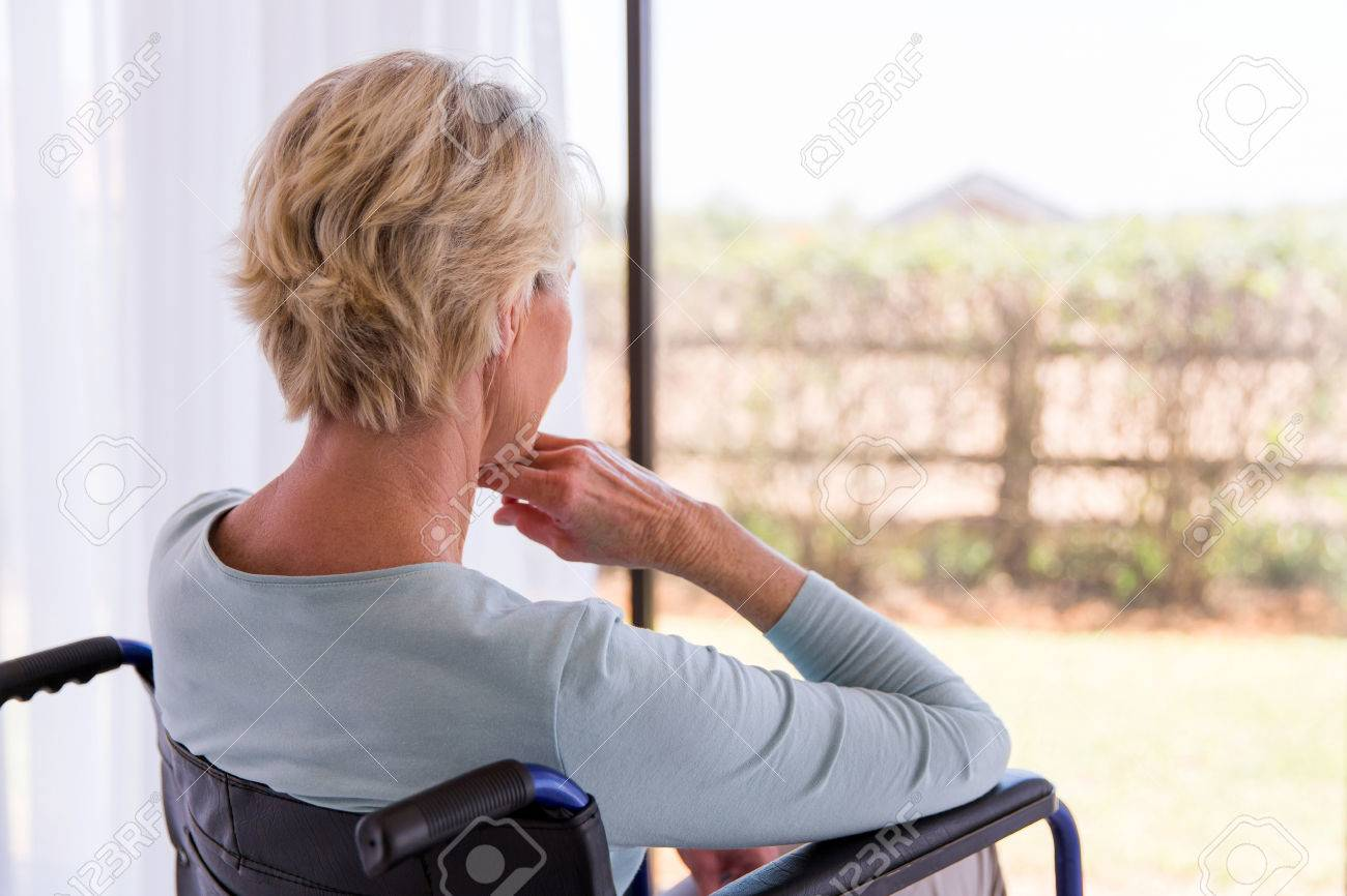 back view of handicapped senior woman looking through window - 53032057