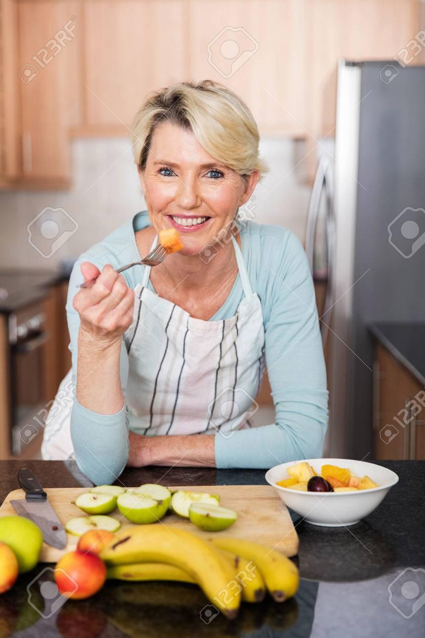 healthy mature woman eating fruit salad at home - 53032832