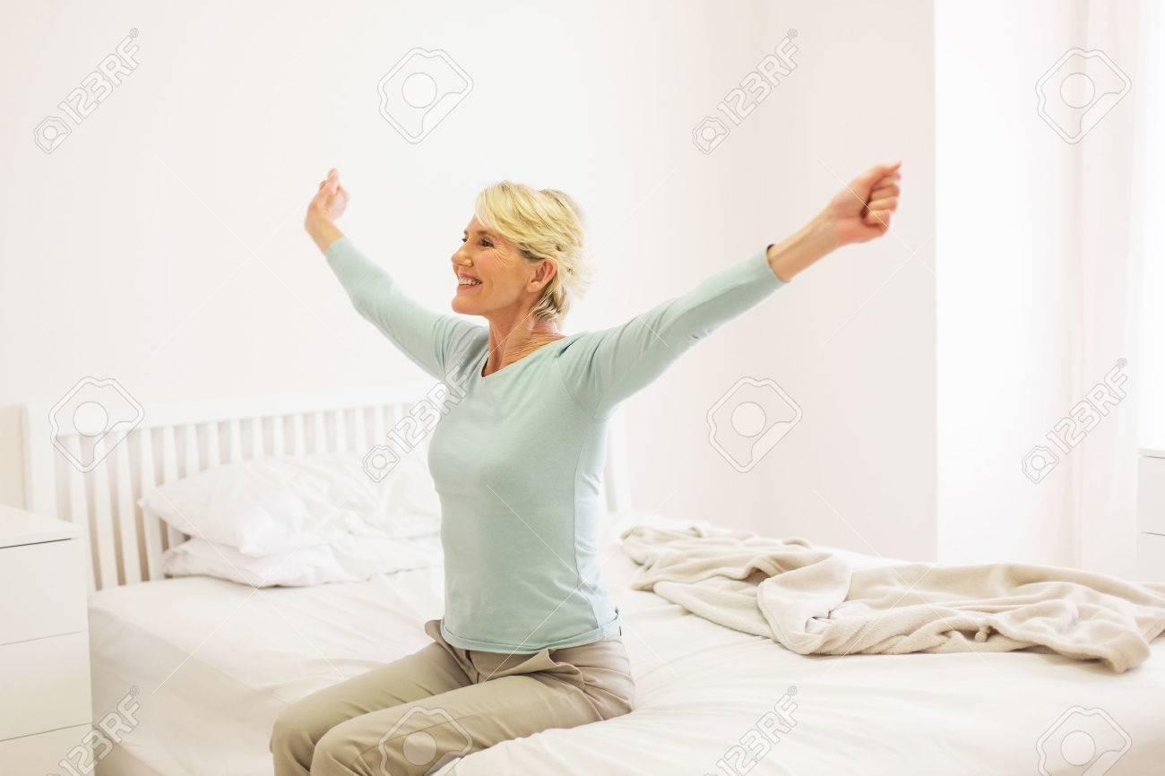 happy middle aged woman getting up - 53032925