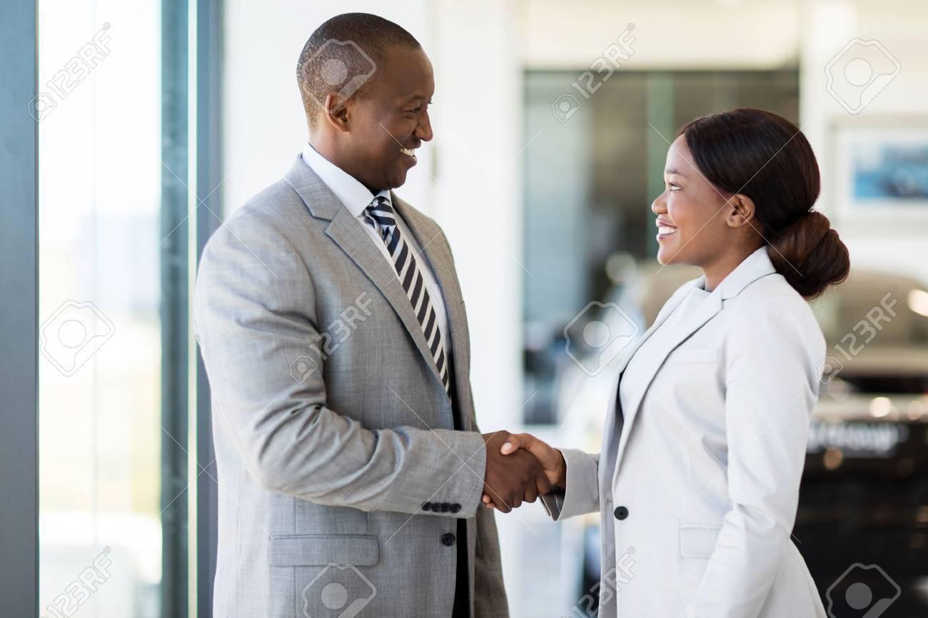 cheerful african car dealer handshake with customer in showroom - 53100353