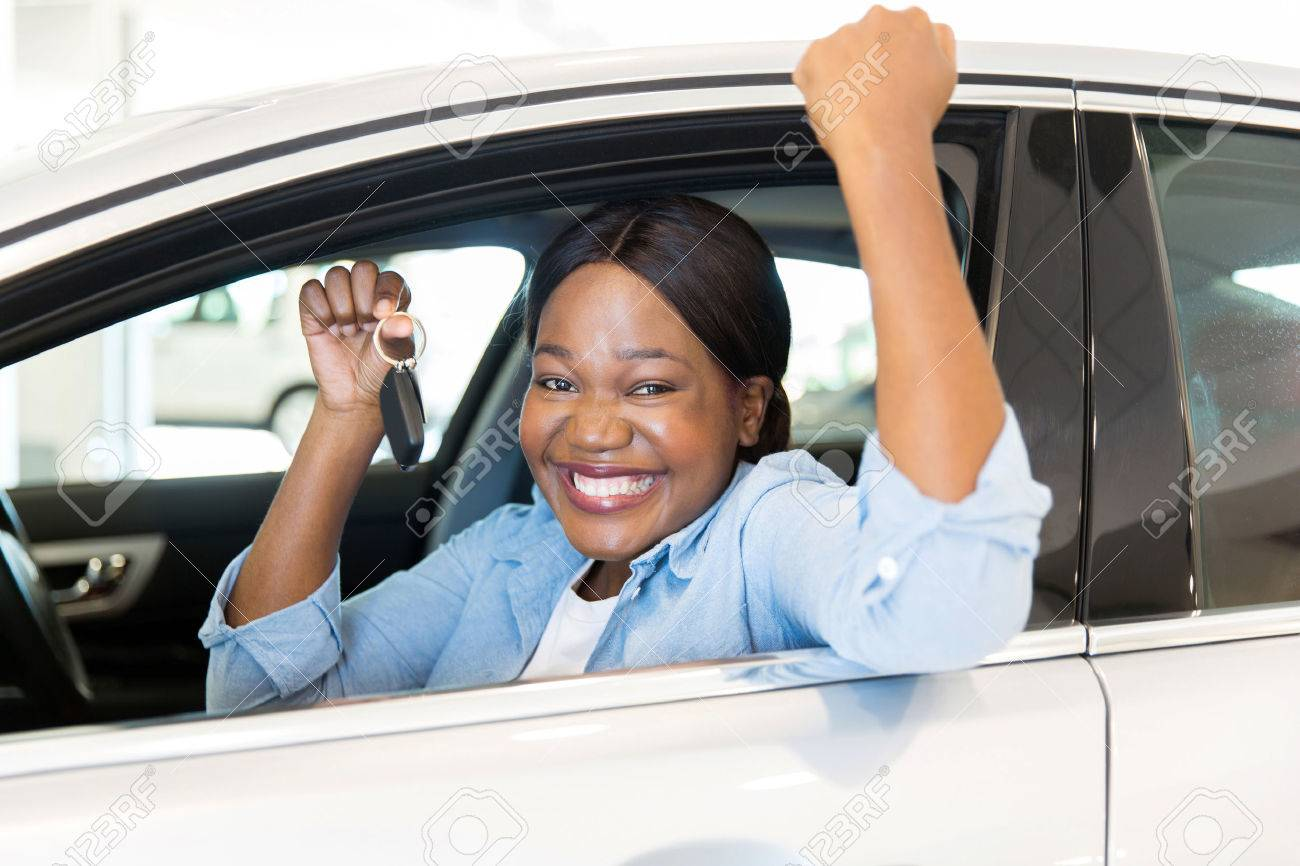 cheerful young african woman showing her new car key at dealership - 53100377