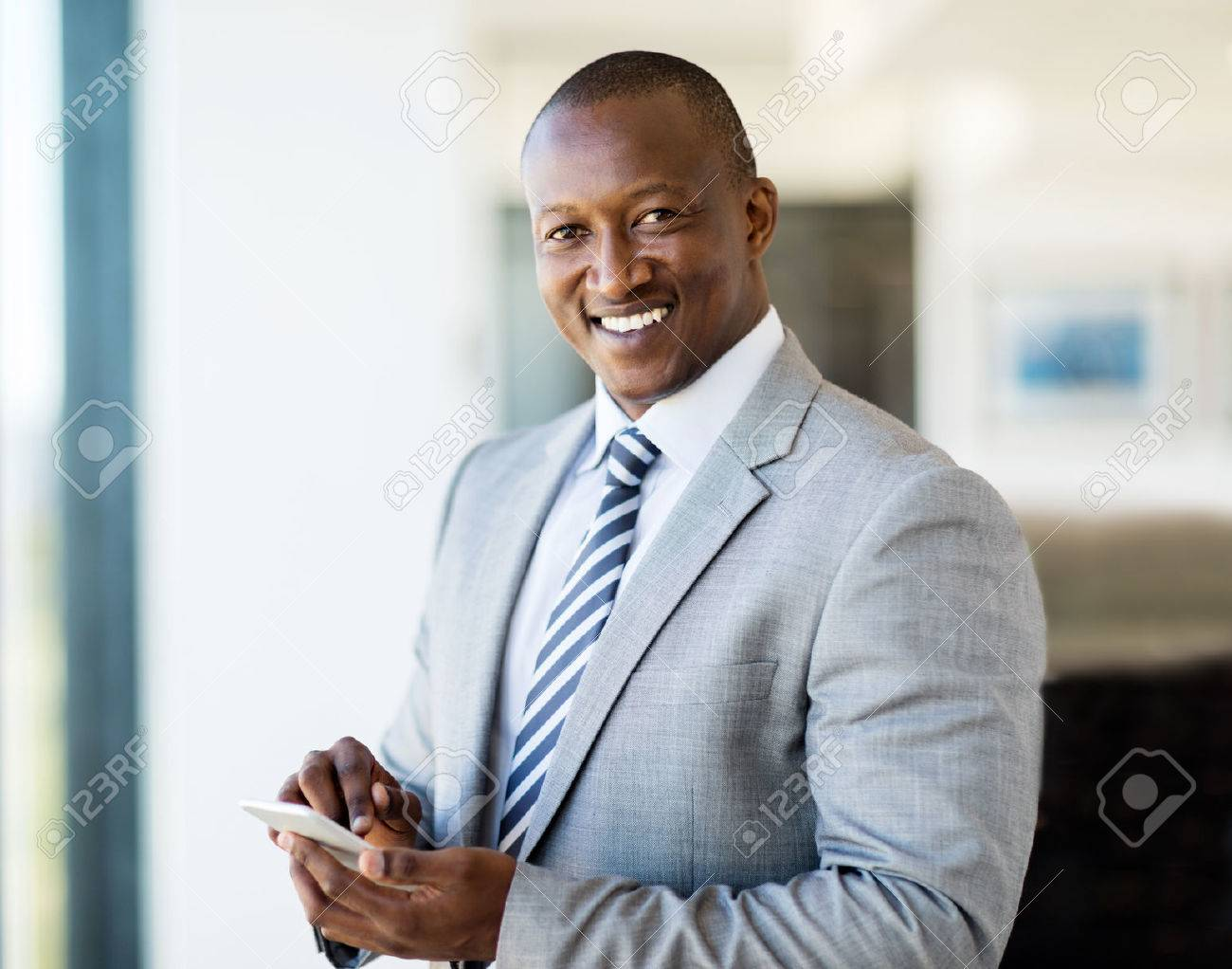 portrait of smiling african businessman using smart phone in office - 53100612