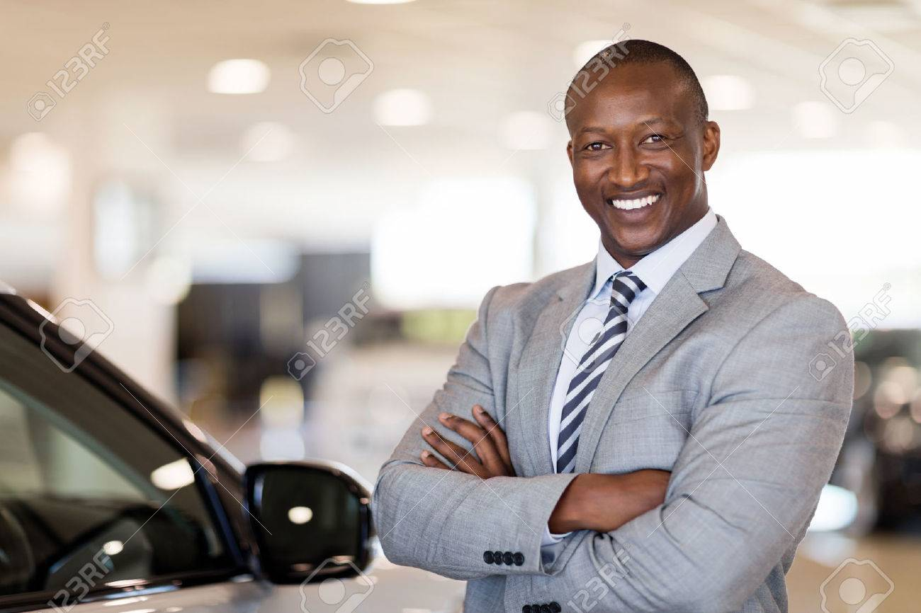 african american car dealership principal standing in vehicle showroom - 53100657