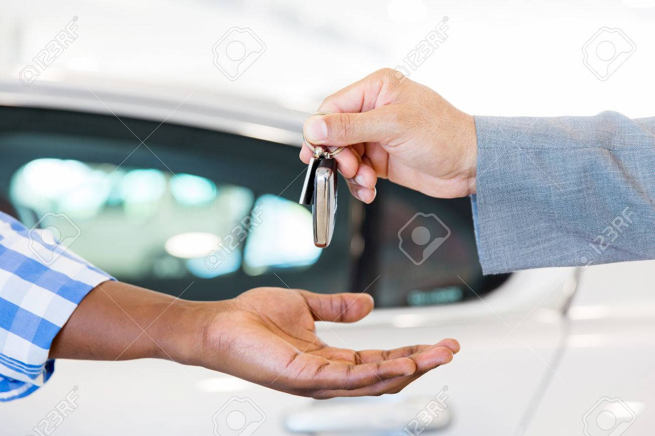 close up of car dealer handing over new car key to customer at showroom - 53100703