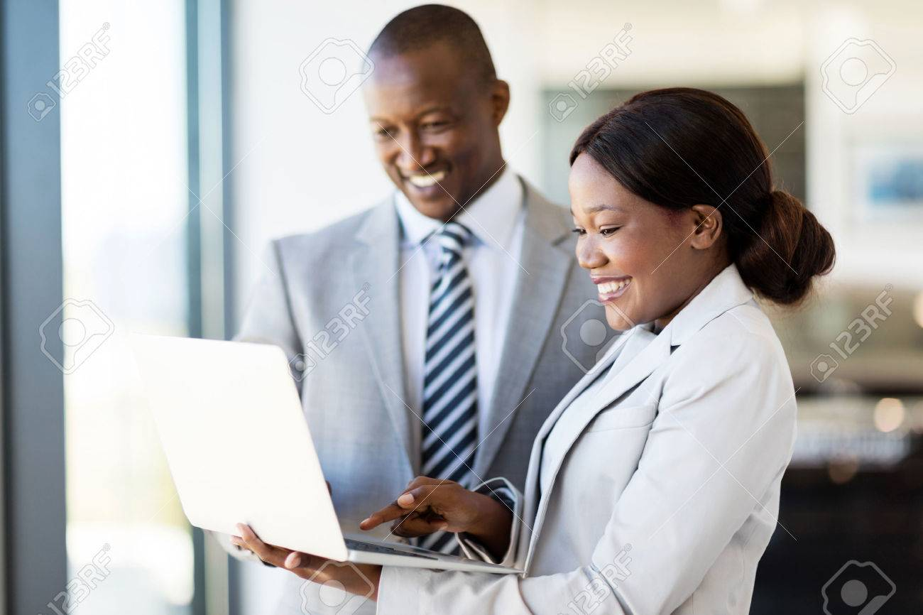 professional car sales consultants working on laptop computer inside vehicle showroom - 53100911