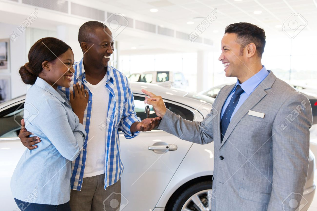mid age car salesman handing over new car key to african couple in car showroom - 53100915