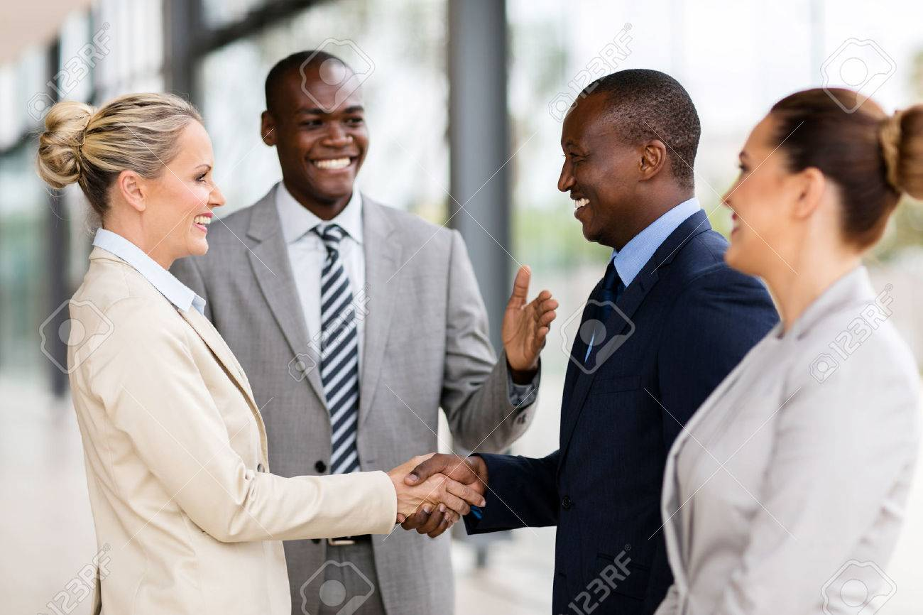 happy african man introducing businesswoman to business partners - 54871381