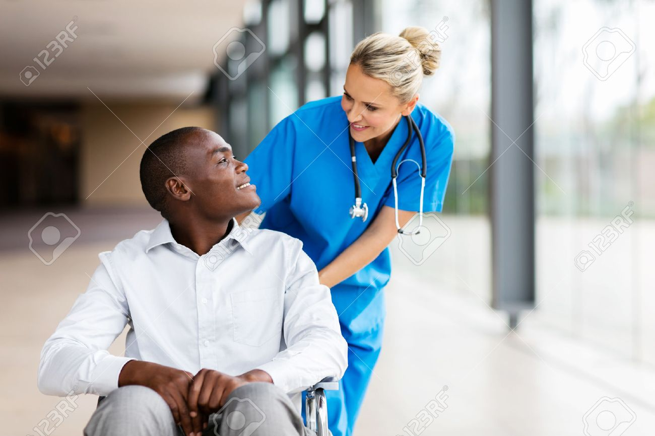 caring female nurse talking to disabled patient in hospital - 54872253