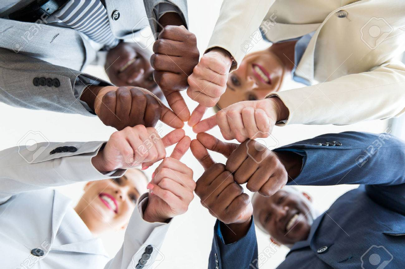 low angle view of multiracial co-workers with thumbs joined together - 54874182