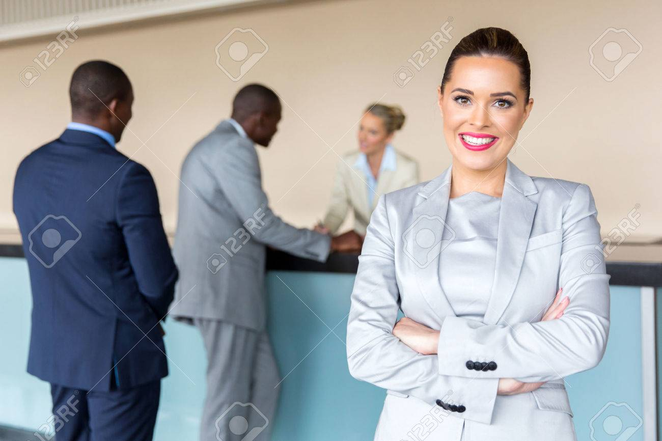 happy young businesswoman standing at hotel reception - 54874631