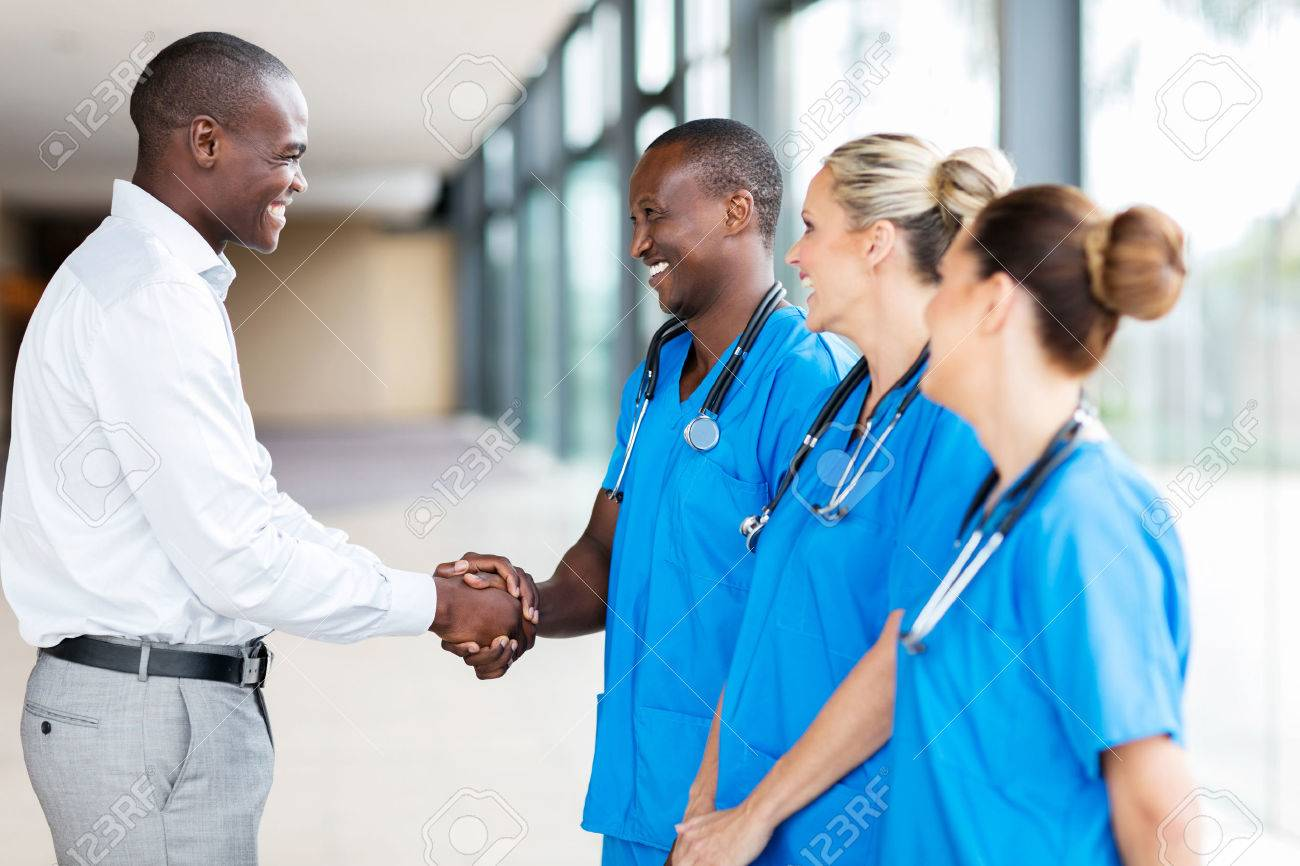 happy medical rep handshaking with group of doctors in hospital - 54874773