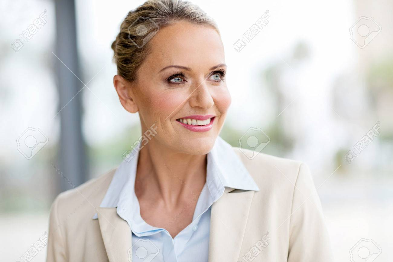 attractive mid age businesswoman looking outside window - 54876475