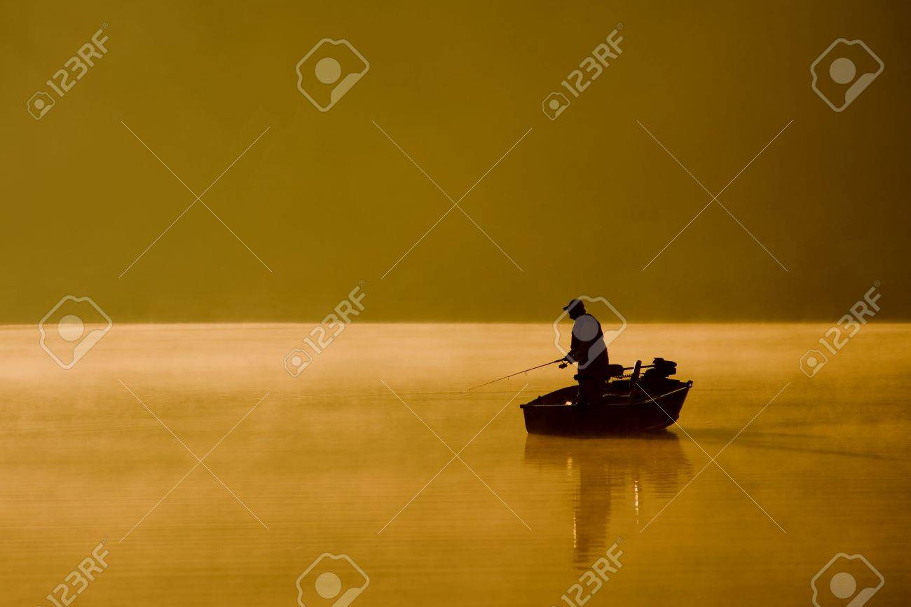 A single angler enjoys fishing from a boat on a beautiful morning. Stock Photo - 8111903