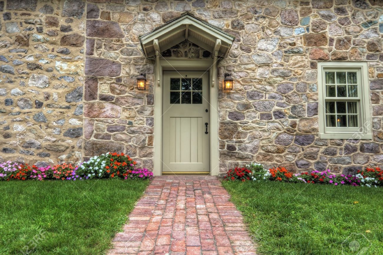 path and door entrance of a stone home with spring flowers and