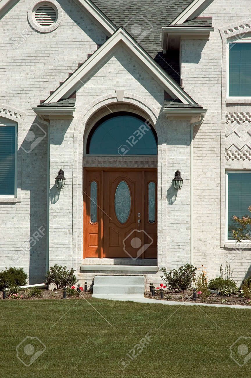 beautiful front door entrance to this new white brick home