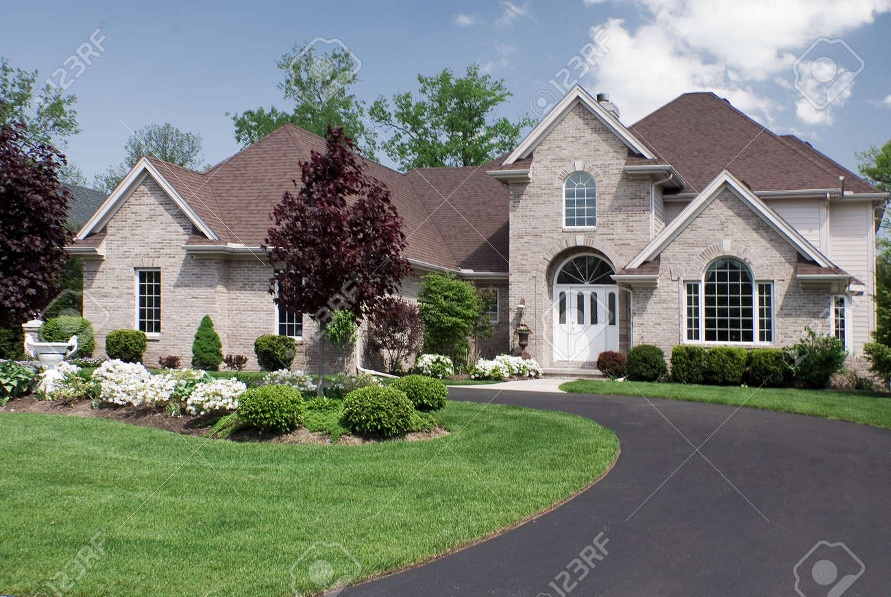 Belle et grande maison de brique marron doté dun design complexe de toiture et laménagement paysager fantastique formelle