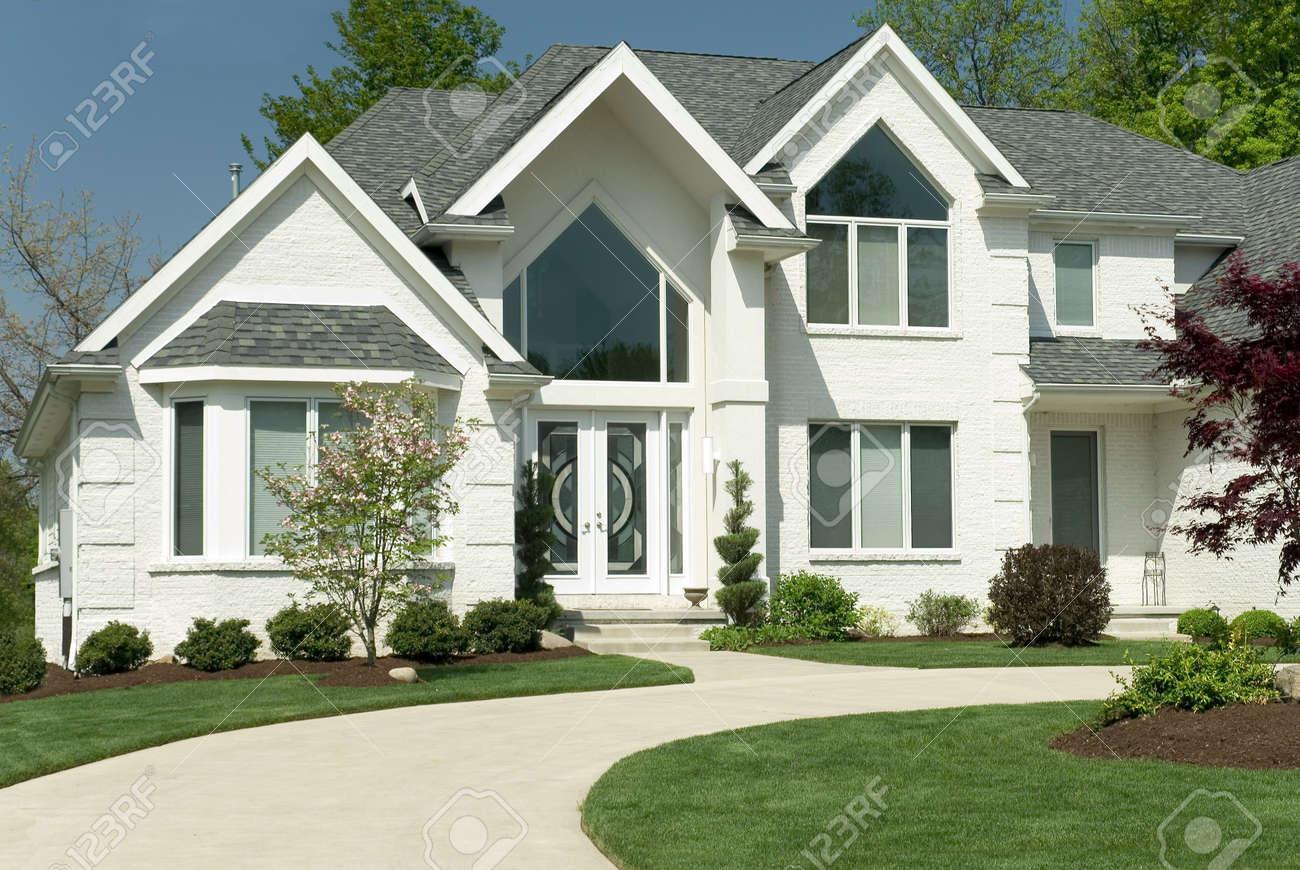 Belle maison en briques blanches avec une conception architecturale moderne  avec de grandes fenêtres et une allée circulaire. Le chantier est ...