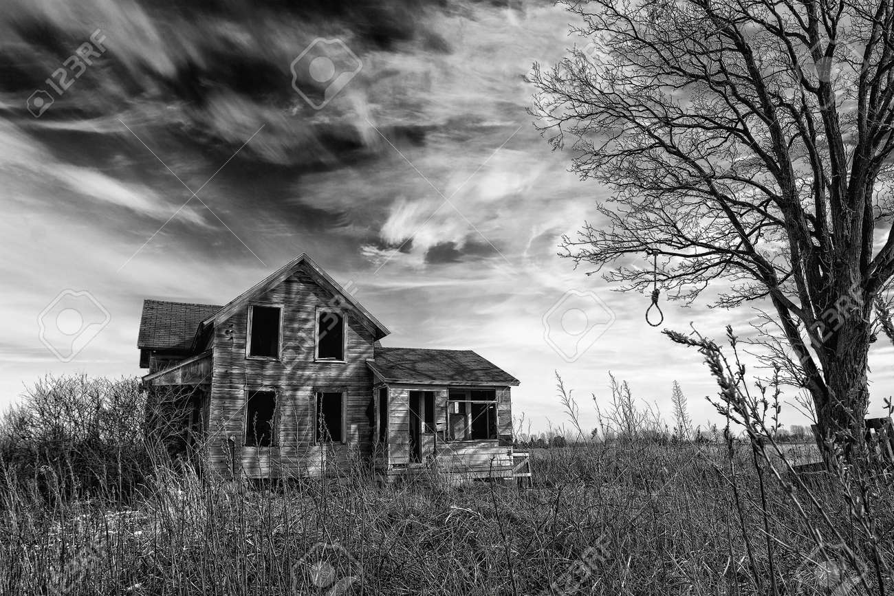Black and white photo of an old scary abandoned farm house that