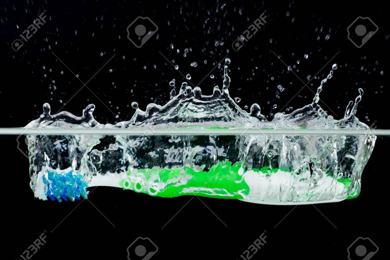 Toothbrush with splashing water on a black background Stock Photo - 13821655