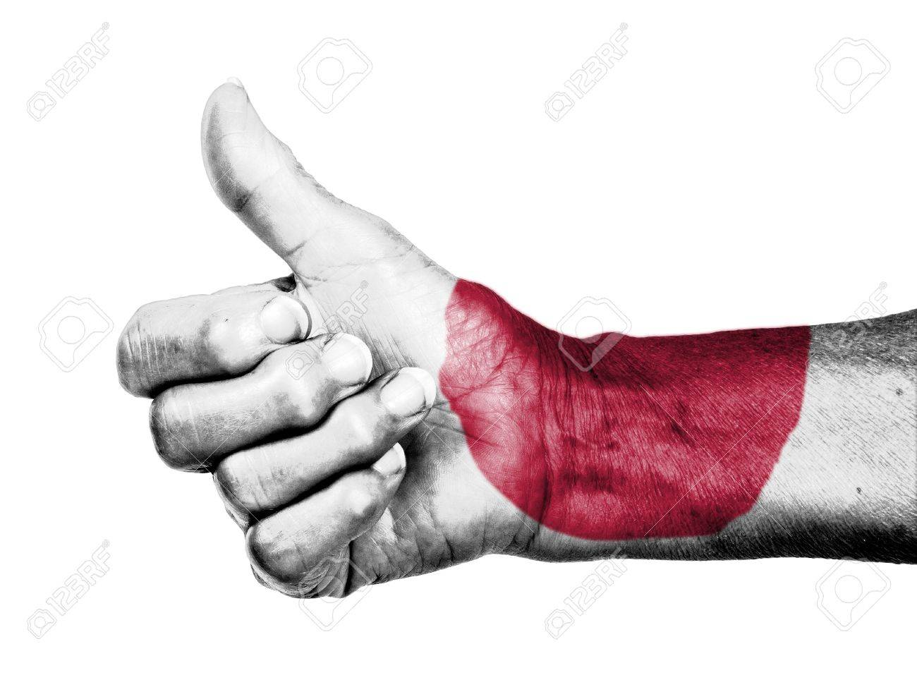 Old woman with arthritis giving the thumbs up sign, wrapped in flag pattern, Japan Stock Photo - 17520108
