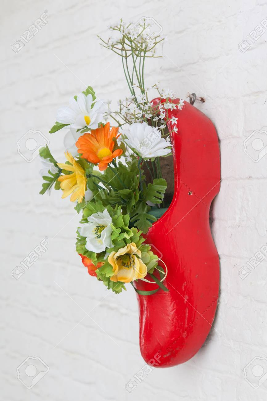 Dutch Wooden Shoe With Fake Flowers Hanging On A White Wall Stock