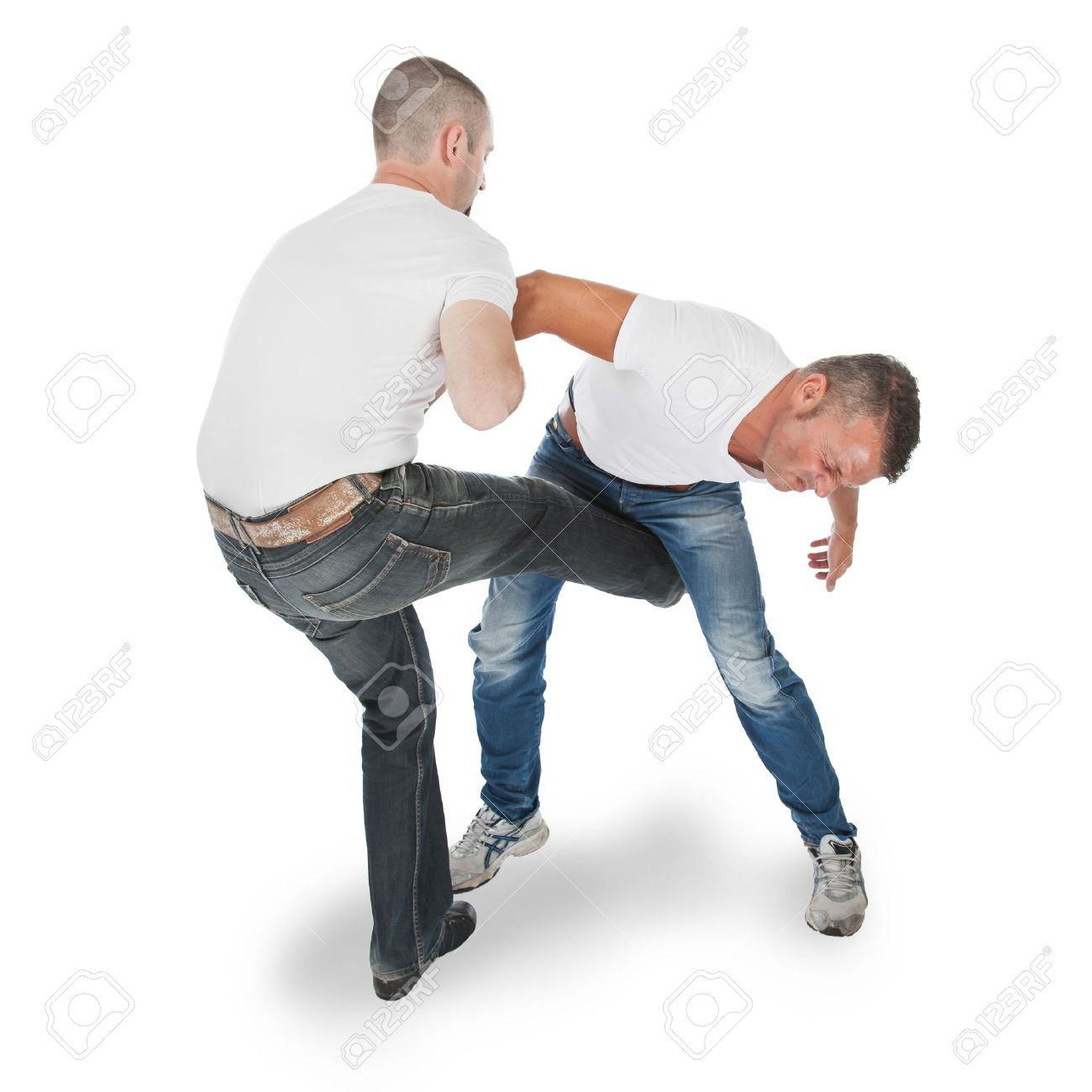 Man defending an attack from another man, selfdefense, kicking in groin, isolated on white Stock Photo - 22875404
