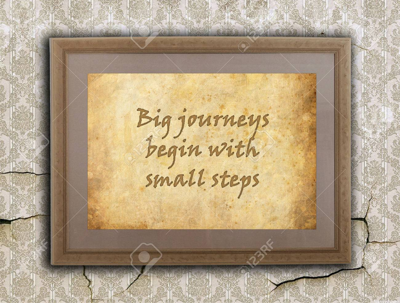 Old wooden frame with written text on an old wall - Big journeys, small steps Stock Photo - 23480776