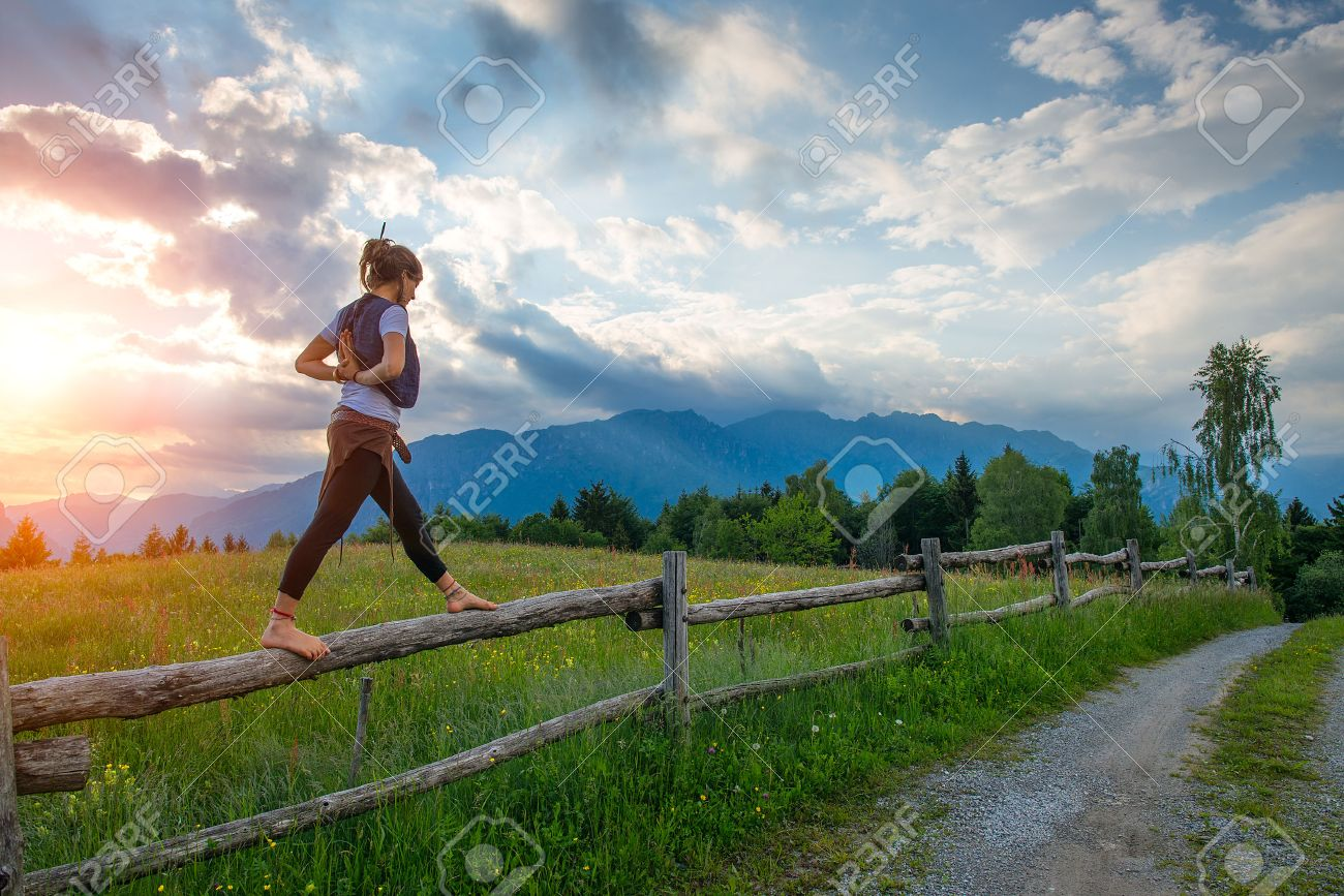 Casual girl relaxes doing stretching and yoga alone in the mountains over a fence in a beautiful spring meadow. - 44574667