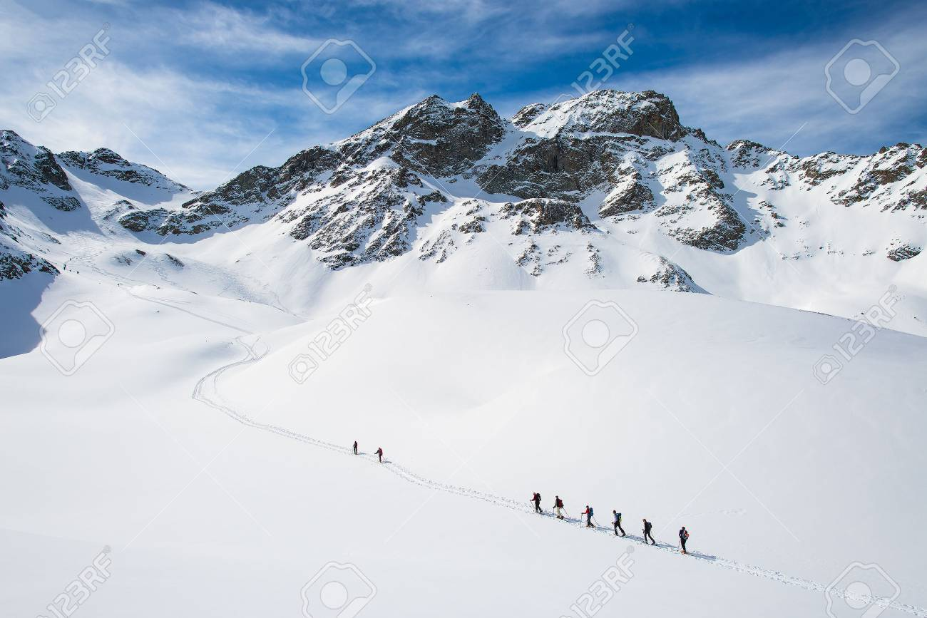 Group of climbers roped to the summit in the winter - 55342542