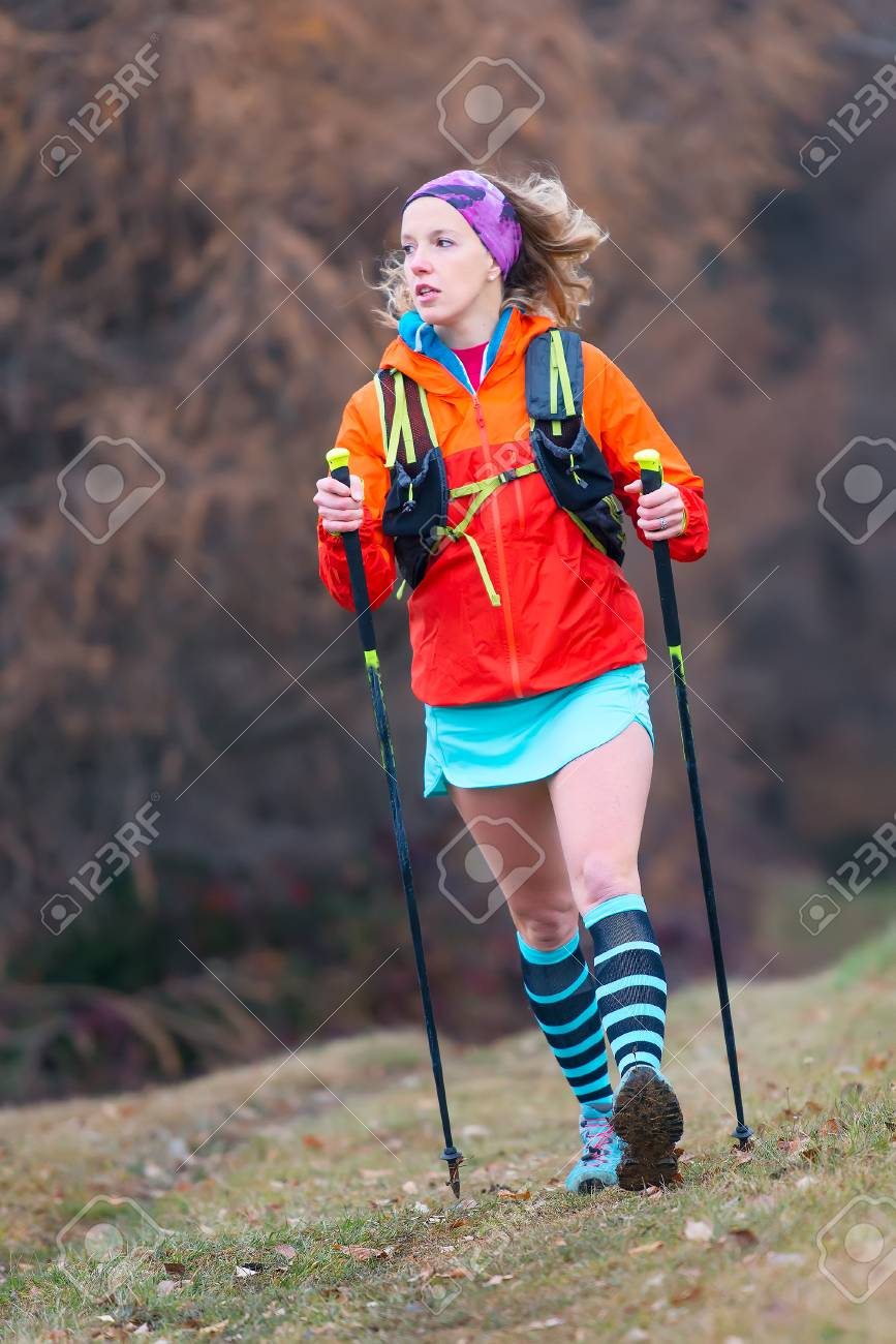 Young sporty blonde girl active practice Nordic walking in a mountain meadow - 66062108