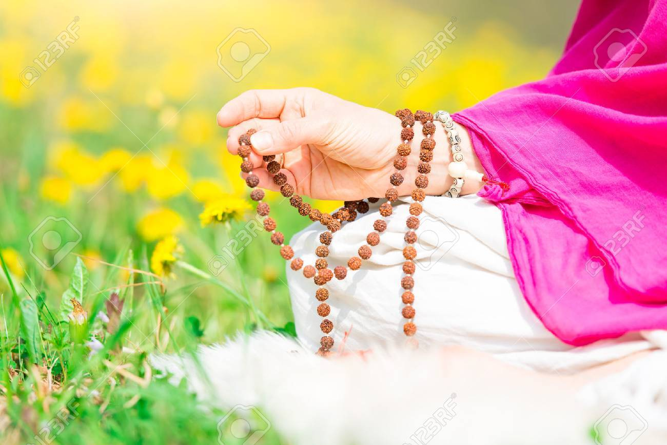Use of Mala with mantras during a yoga practice flourished in nature - 76066088