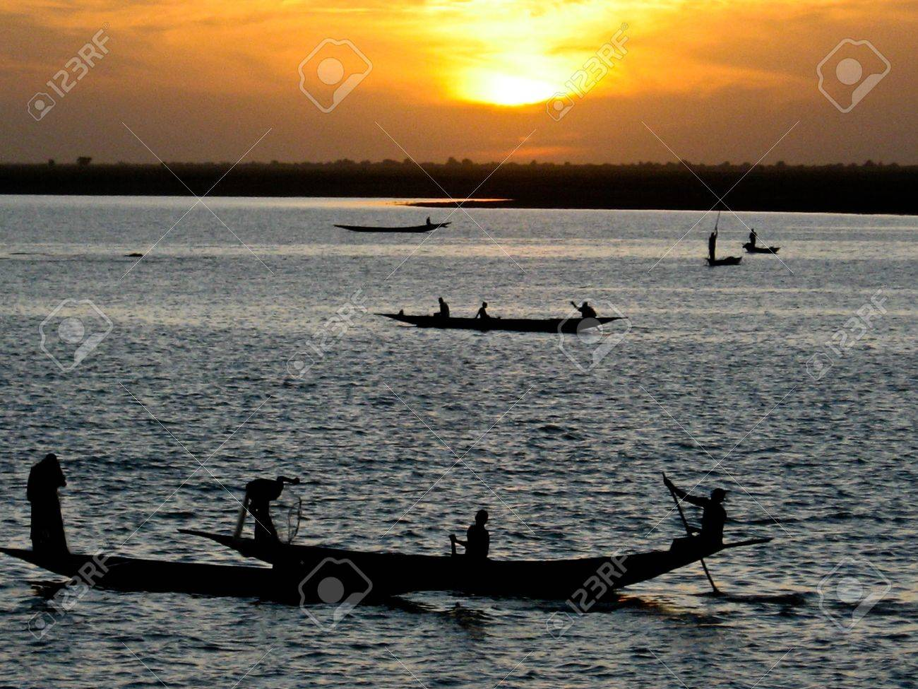 Fishermen in a pirogue in the river Niger at sunset.The Niger River is an important source of fish, providing food for riverside communities. Stock Photo - 10935938