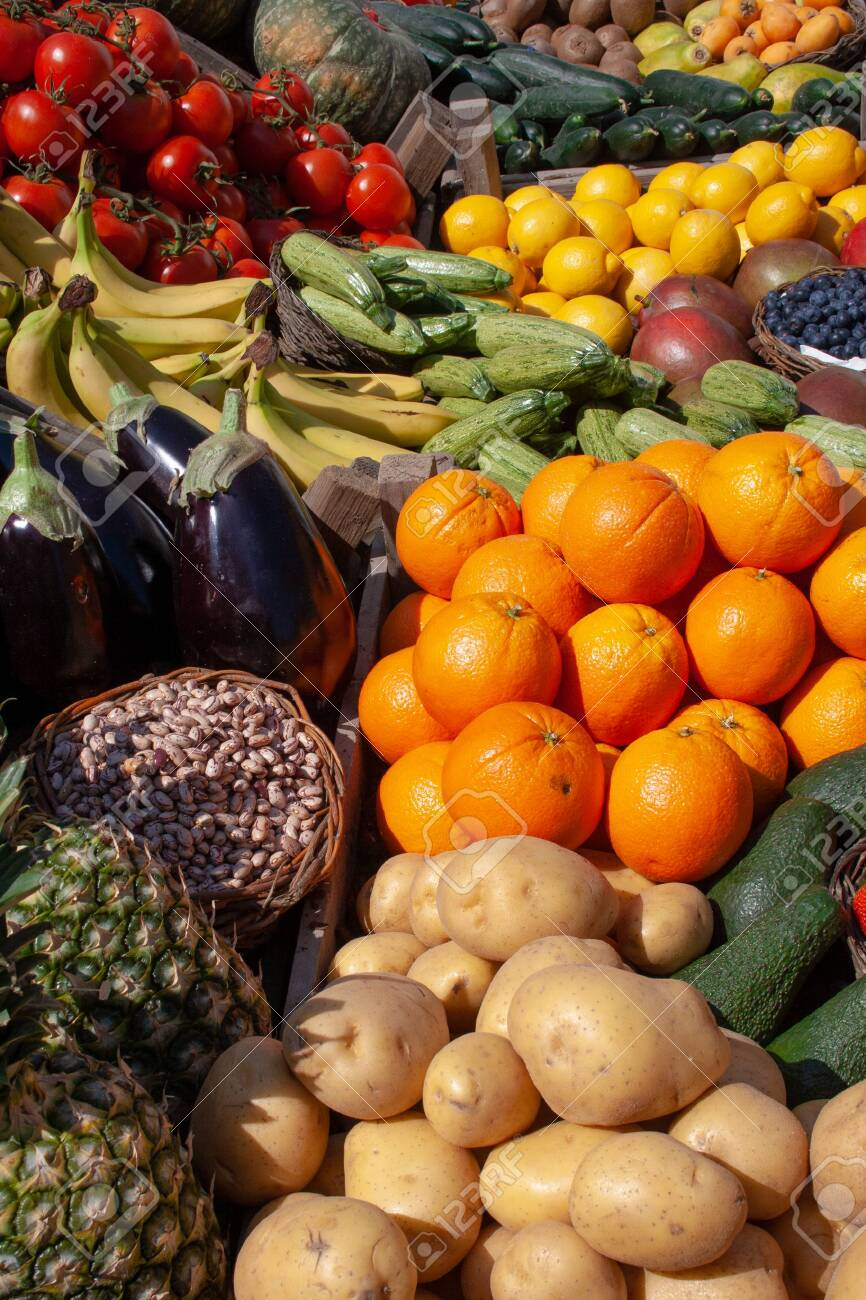 Beautiful composition of various fresh fruits and vegetables in wooden boxes in a market - 121864327