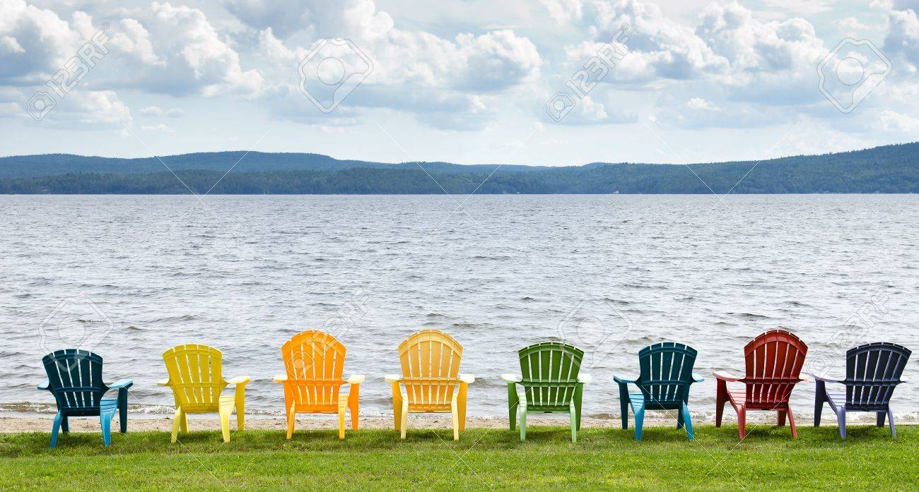 Eight Colorful Adirondack Chairs Lined Up On The Beach Looking Out On The  Lake, Mountains