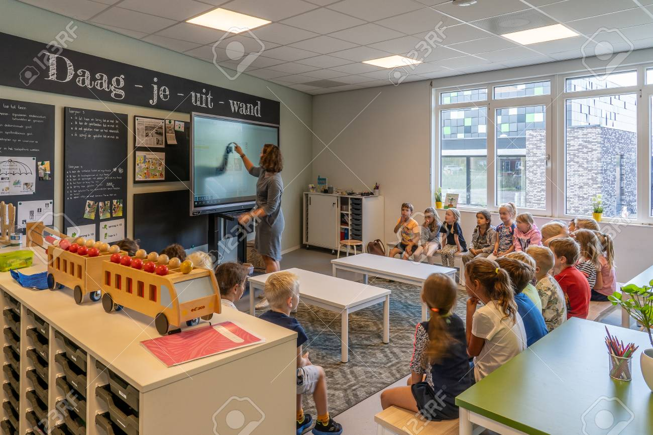 NIJMEGEN / NETHERLANDS-SEPTEMBER 13, 2019: Modern school building for children up to 12 years old. The children sit in the classroom where they receive instruction from the teacher. - 132984078