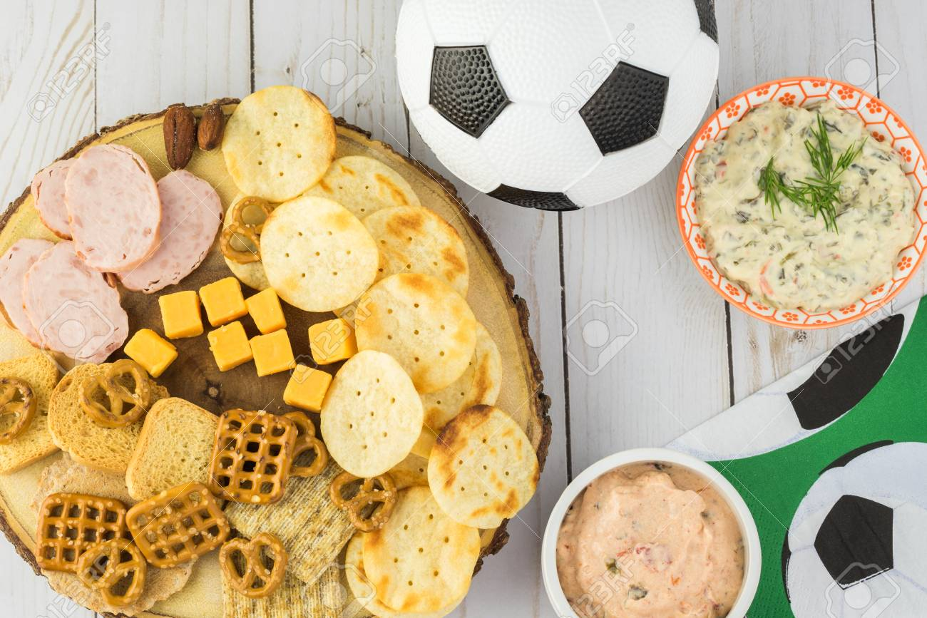 top view of party table with variety of snacks and dips for soccer
