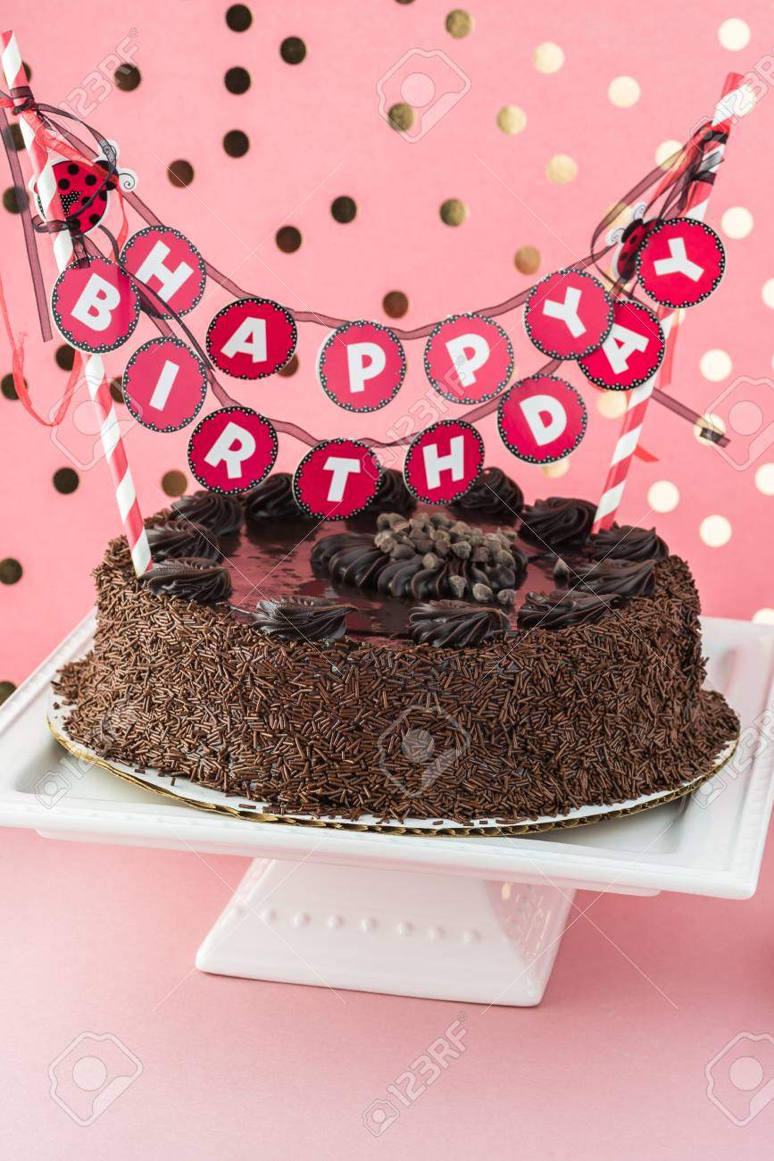 Close Up Of Chocolate Birthday Cake With Happy Banner Stock Photo