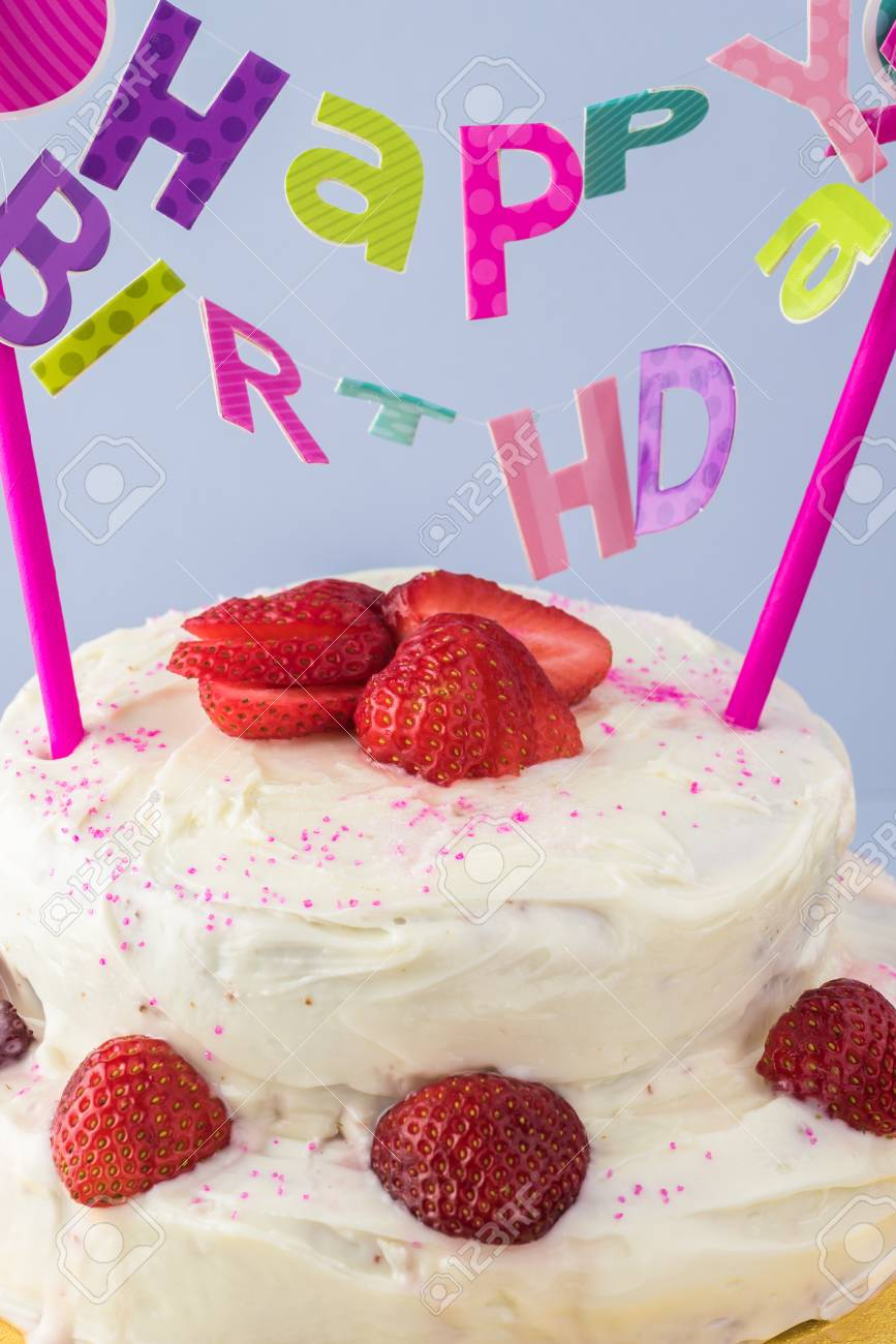 Close Up Of Homemade Strawberry Cake With Happy Birthday Banner Stock Photo
