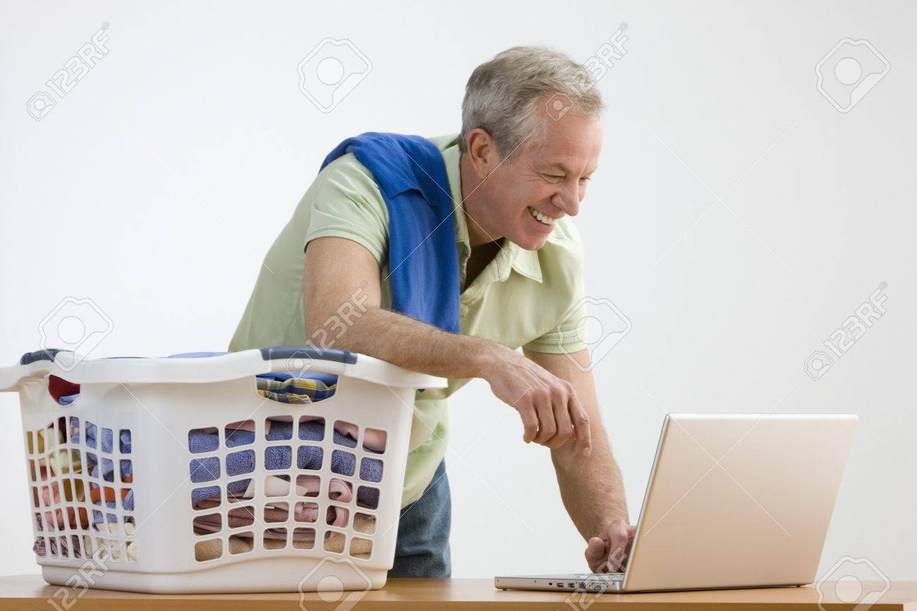 A man is working on a laptop while he folds laundry.  He is smiling and looking away from the camera.  Horizontal shot. Stock Photo - 7467402